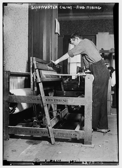 Black and white historical photo of a man working at a loom
